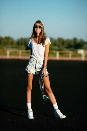 A young beautiful teen posing  with a sunglasses on  and her skateboard.