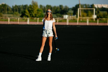A girl standing   on a sunset with her sunglasses on while holding a skateboard.