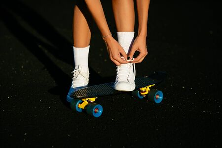 A girl tying her white shoes near a skateboard. Banco de Imagens