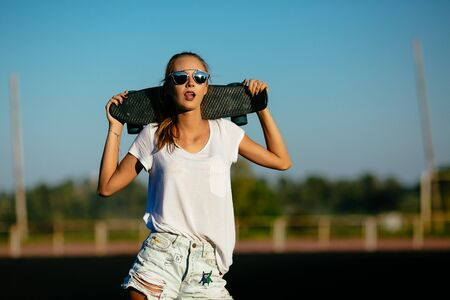 Cheaky faced girl  with a skateboard with sunglasses on. Banco de Imagens