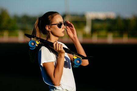 A good looking girl  with a skateboard on her shoulder checks her sunglasses. Banco de Imagens