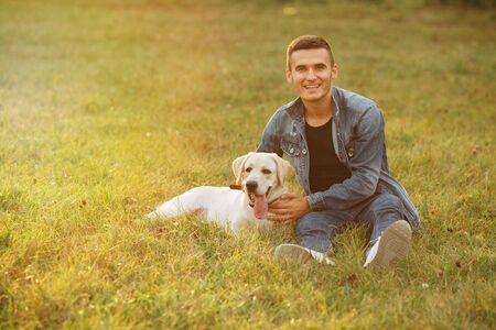 Portrait of smiling guy and his dog Labrador sitting on grass in park at sunset