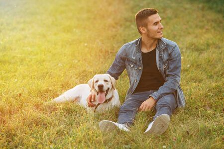 Portrait of sitting man and lying dog Labrador on grass in park at sunset Banco de Imagens