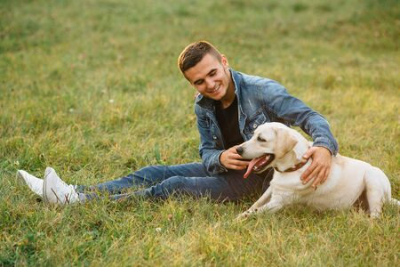 Smiling man sitting on grass with his dog labrador in park Banco de Imagens - 129734463