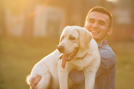Happy man holding his dog labrador in hands in park at sunset. Toned photo
