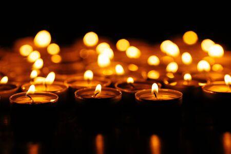 Brennende Kerzen. Viele brennende Kerzen leuchten im Dunkeln. Geringe Schärfentiefe. Standard-Bild