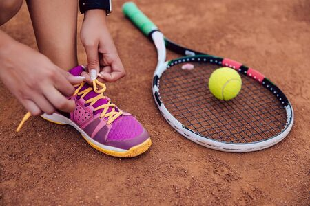 Sportive woman getting ready for playing a game of tennis, tying shoelaces. Close-up view.