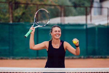 Tennis player. Cheerful beautiful girl playing tennis, prepares to serve a tennis ball. Dressed in black t-shirt.