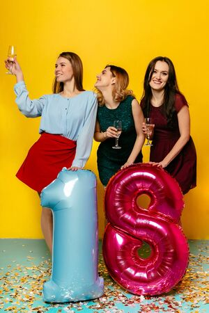 Happy 18th birthday. Happy young stunning girls having fun together while celebrating a holiday with champagne and balloons, isolated over yellow background. Archivio Fotografico