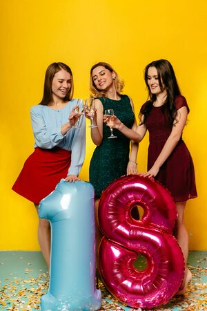 Attractive young women drinking a champagne, toasting, holding balloon in form of eighteen, celebrating birthday party. Indoors, isolated on yellow background.