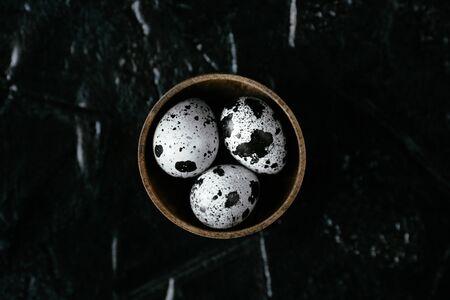 Quail eggs. Raw quail eggs in container. Three quail eggs on black background