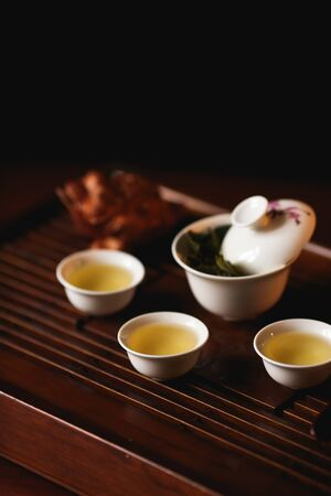 Chinese tea ceremony. Tea set on tea desk chaban with golden frog.  Soft selective focus.