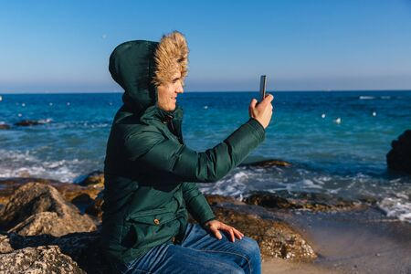 Smiling young man taking a selfie on cell phone near the sea. Dressed in warm jacket with fur hood. Outdoors. Banco de Imagens