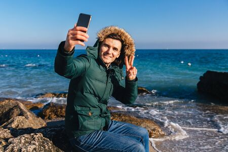 Happy handsome man takes a selfie on smartphone, showing gesture of peace on the background of the sea. Dressed in warm jacket with fur hood. Banco de Imagens