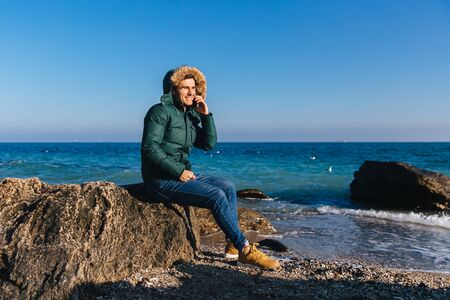 Happy attractive guy talking on the cell phone while sitting on the stone near the sea. Cold weather. Outdoors. Banco de Imagens