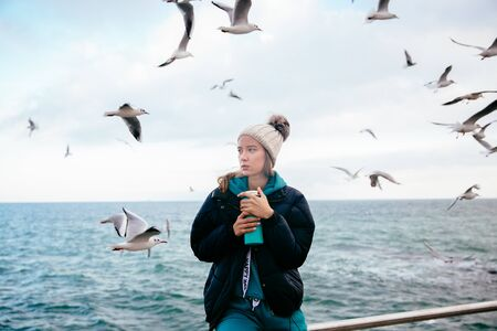 Attractive young woman thinking about something,   near the ocean with seagulls Banco de Imagens