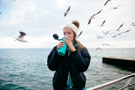Young attractive woman standing near the sea and drinking tea  , on the background of seagulls. Banco de Imagens