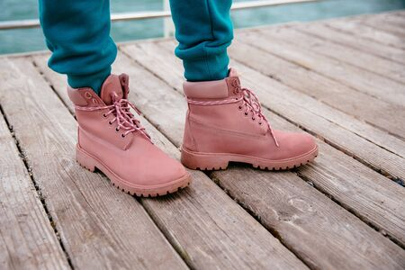 A close-up picture of females pink suede boots, outdoors.