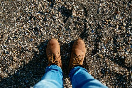 Top view on brown mens boots, on the stone beach. Sea stones background.