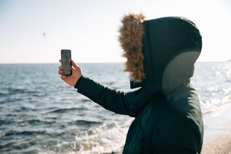 Young man, taking a selfie on the beach, dressed in warm jacket with hood. Banco de Imagens