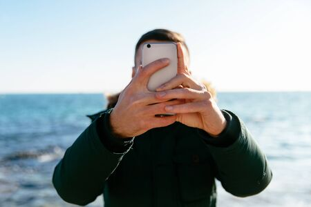 Young man taking a selfie against the background of the sea, on grey smartphone.