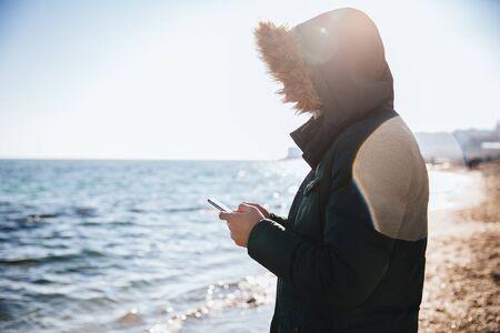 Young man using mobile phone, typing message, on the beach by the sea.