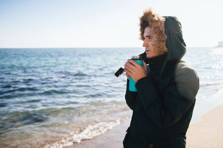 Handsome young man warming with tea  , looking at the sea, dressed in jacket with hood