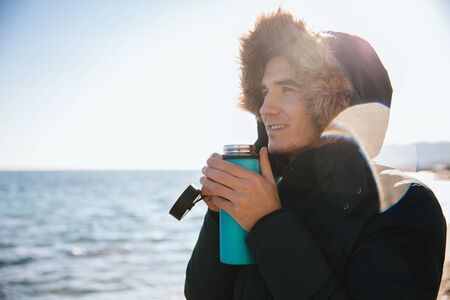 Handsome happy young man drinking tea,   looking at the sea, dressed in jacket with hood.