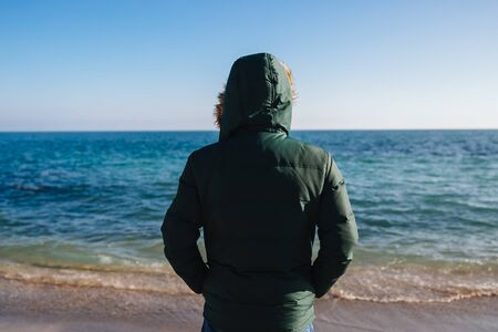 Young man looking at the sea, dressed in warm jacket with hood. Back view.