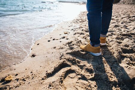 Close-up of mens legs, standing on the sand by the sea. Dressed in jeans, brown boots.