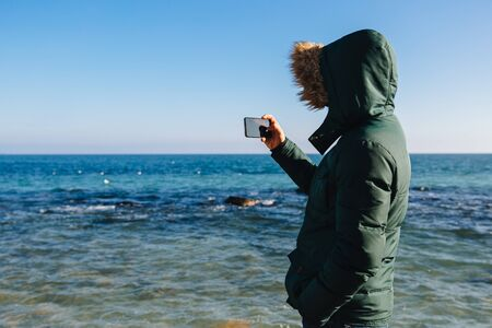 Young man taking a picture of the seascape on smartphone, outdoors. Back view.