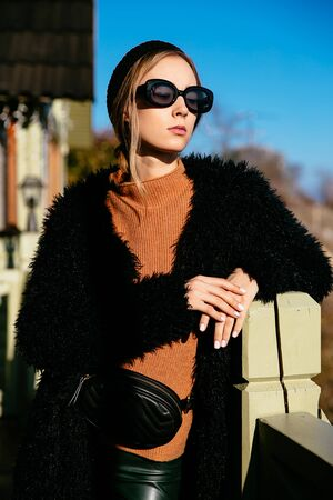 Attractive woman in black soft coat, in exclusive sunglasses, posing, outdoors Stock Photo