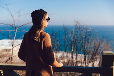 Dressed stylish young woman in black sunglasses looking at the sea, dreaming about something. Back view.
