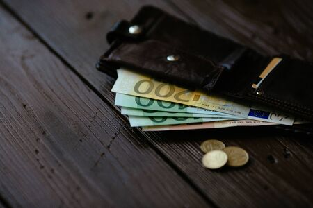 Open wallet with Euro cash and Euro cents on wooden background. Male wallet with Euro cash