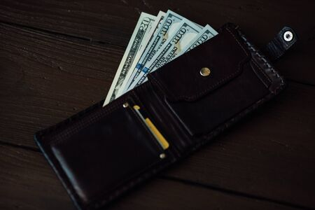 Wallet with dollars cash. Open wallet with dollars banknotes and credit cards on wooden background Banco de Imagens