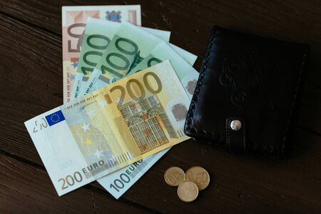 Wallet and Euro cash. Brown male wallet and euro banknotes with euro cents on wooden background