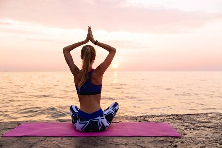Yoga at sunrise. Back view of sportive woman, practicing yoga, sitting on pier in lotus position, looking at sea. Dressed in sportswear.