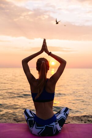 Yoga. View from back of young woman in sportswear, is engaged in yoga, sitting on pier in lotus pose, meditating, looking at sea sunrise.