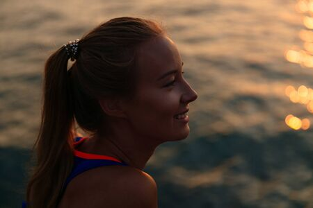 Side view of a smiling beautiful woman in sport singlet, resting near the sea, enjoying the landscape. Close-up.