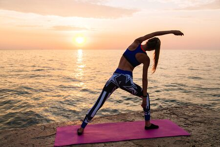 Yoga at sunrise. Back view of sportive woman doing exercises for body, practicing yoga, on the pier, near the ocean at sunrise. Dressed in leggings and sport singlet.
