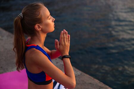 Yoga at sunrise. Side view of sportswoman sitting in lotus position, keeping her hands together, meditation, practicing yoga on the pier, near the sea at sunrise. Dressed in leggings and sport clothes.