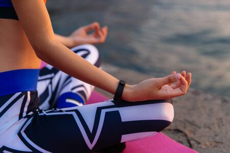 Yoga time. Close-up outdoor photo of woman hands during meditation, trying to calm down, wearing sport leggings and singlet. Banco de Imagens