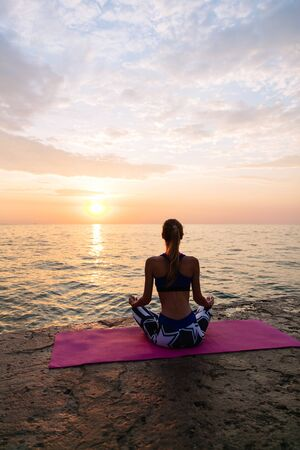Yoga time. Healthy lifestyle concept. Back view of sportive woman meditating in lotus pose, sitting on the pier, looking at sea sunrise.