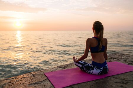 Yoga at sunrise. Attractive woman in sportswear, is engaged in yoga, sitting on pier in lotus pose, meditating, looking at sea sunrise. Fitness concept.