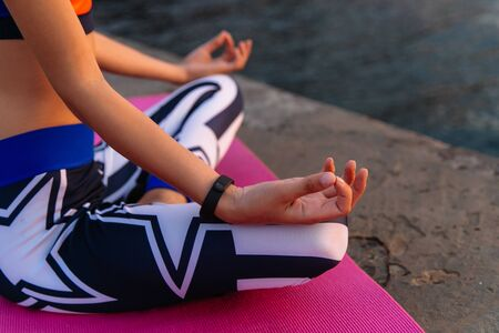 Yoga. Close-up outdoor photo of woman hands during practicing yoga, meditation, wearing sport leggings and singlet. Healthy concept. Banco de Imagens