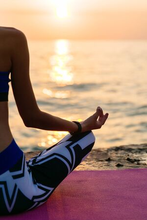 Yoga at sunrise. Back view of a half body of sportive woman, sitting in lotus pose, enjoying yoga and meditation. On pier, near the sea at sunrise.