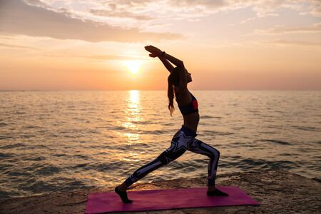 Yoga time. Healthy attractive woman doing exercises for body, practicing yoga, standing against the sunset sea background. On pier. Dressed in leggings and singlet.