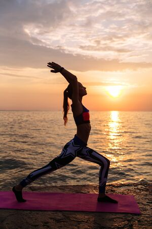 Yoga at sunrise. Prifile of attractive woman doing exercises for body, practicing yoga, standing against the sunrise sea background. On pier. Dressed in leggings and singlet.