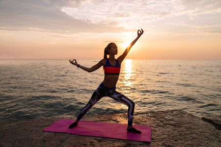 Yoga at sunrise. Young amazing woman exercising on the beach, practicing yoga at beautiful sunrise. Healthy concept. Banco de Imagens