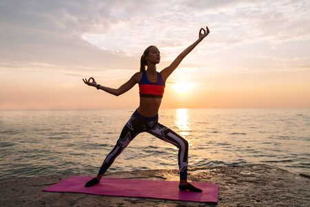 Yoga time. Full length view of sportive concentrated woman exercising on the beach, practicing yoga at beautiful sunset, near the ocean. Healthy concept.